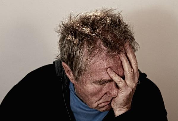 Depressed older man in blue turtleneck and black sportscoat