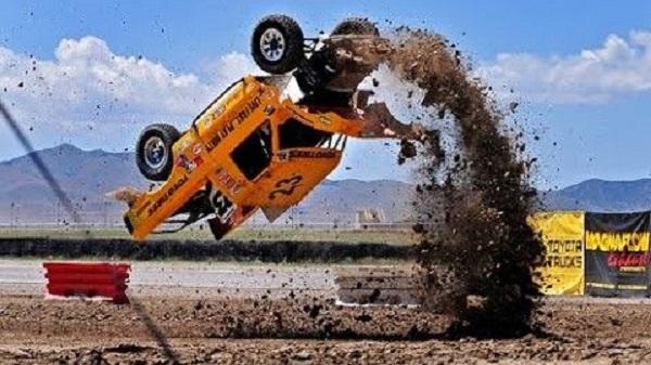 yellow race Car flipping upside down in dirt