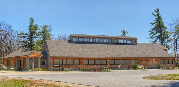The Beaver Island Rural Health Center, a ristic ranch style building with rough shingle siding on a beutiful sunny day